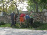 starosta učí mládež připravovat chvojí a motat věnec